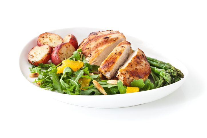 Roasted chicken breast and potatoes with asparagus and salad. Isolated on white with soft shadow and reflection.