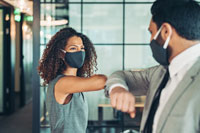 Stock Photo of two people wearing masks giving an elbow bump.